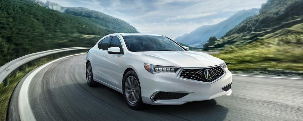 white 2018 acura tlx driving around highway curve