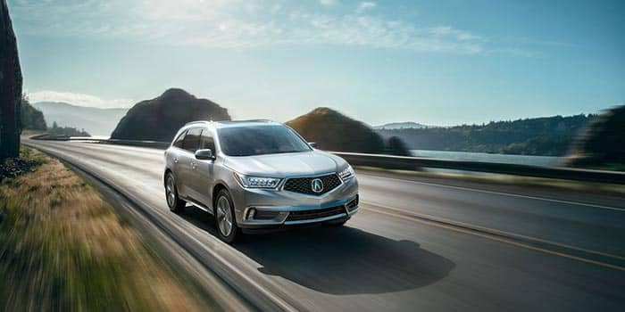 2018 Acura MDX driving on a highway by the lake