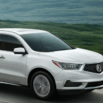 2020 acura mdx white suv driving on highway