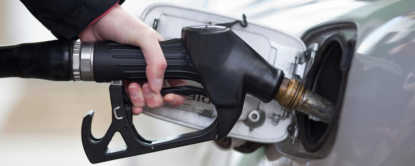 close up of hand pumping gas into vehicle