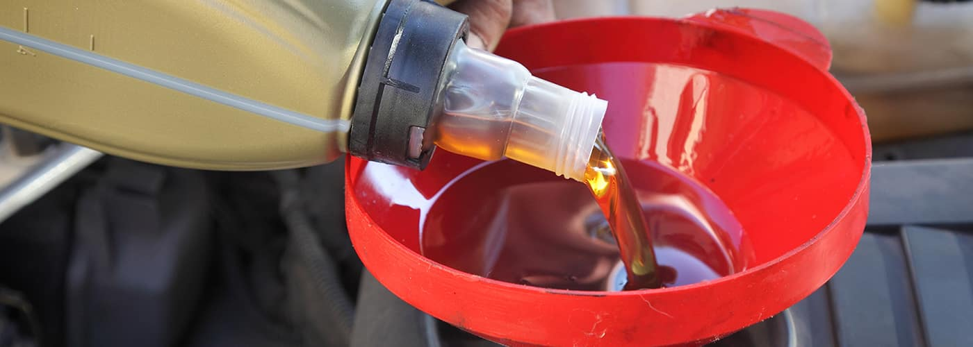 Car servicing mechanic pouring fresh oil to engine
