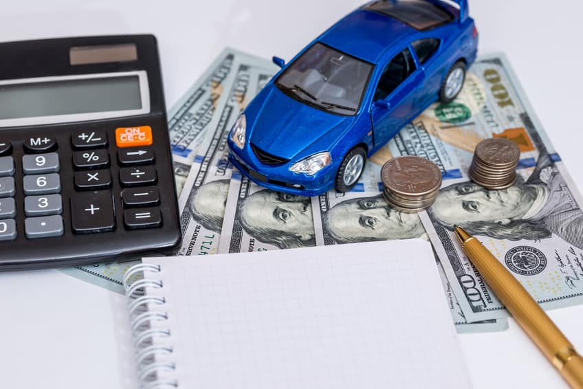 A toy car with cash and a calculator on a stack of car financing papers.