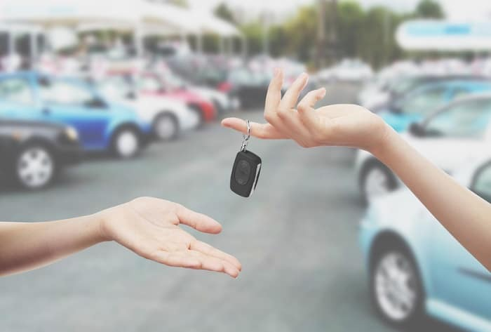 Exchanging keys for a new car at an auto dealership.