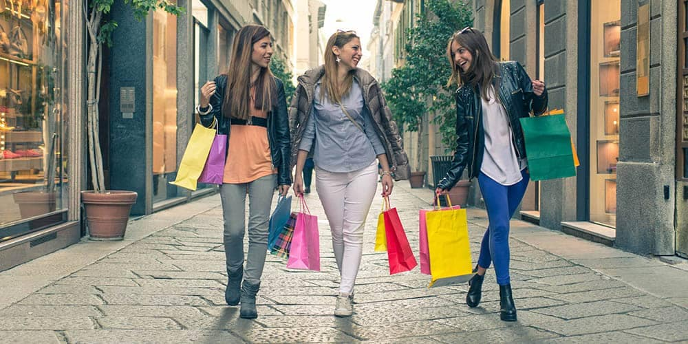 Three girlfriends walking with shopping bags