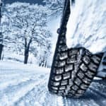 close up of tire on snowy ground with snow-covered trees in background
