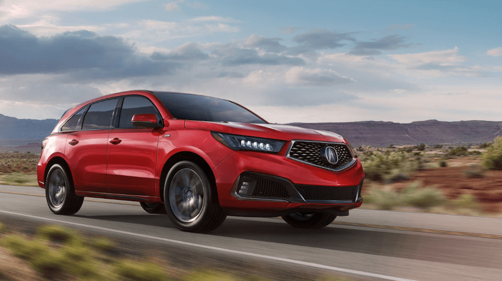 2019 Acura MDX red SUV driving on rural road