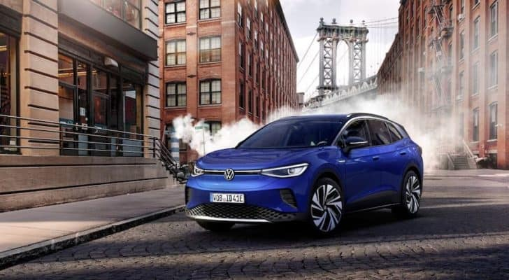 A blue 2021 Volkswagen ID.4 is parked on a cobblestone street in front of steam and the Manhattan bridge.