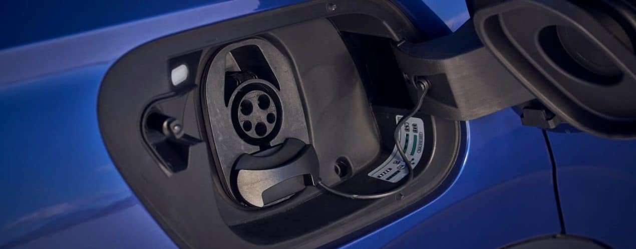 A closeup shows the charging port on a blue 2021 Volkswagen ID.4.
