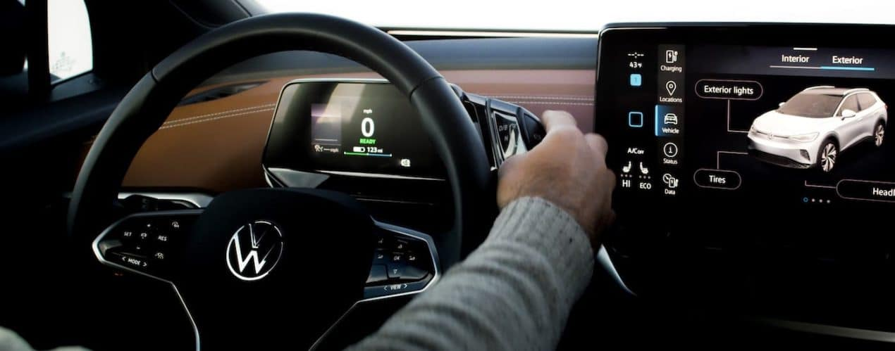 A closeup shows hands on the steering wheel of a 2021 Volkswagen ID.4.