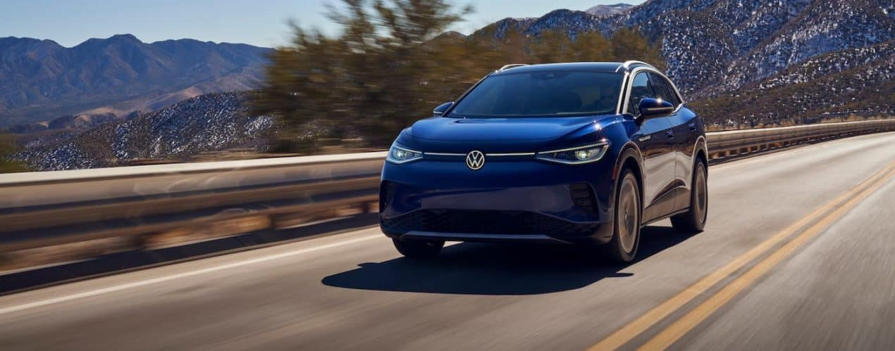A blue 2021 Volkswagen ID.4 is driving on a highway past mountains.