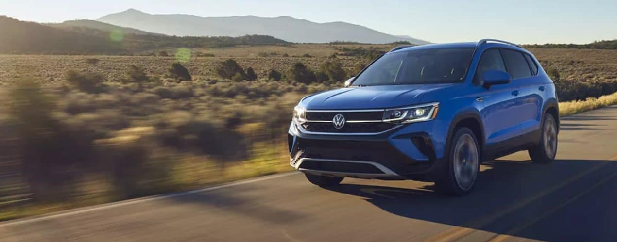 A blue 2022 Volkswagen Taos is driving past desert mountains.