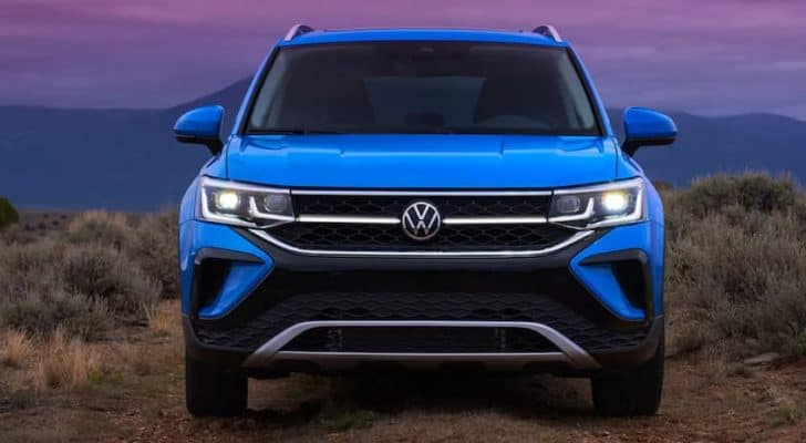 A blue 2022 Volkswagen Taos is shown from the front at the end of a sunset.