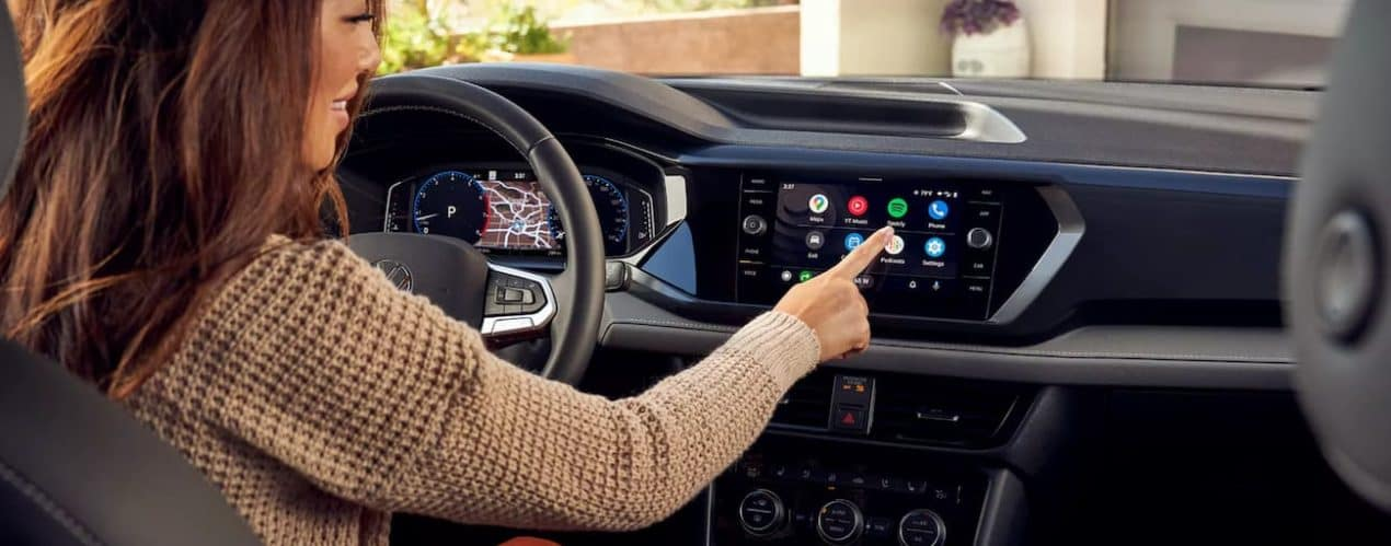 A woman is using the touch screen in a 2022 Volkswagen Taos.