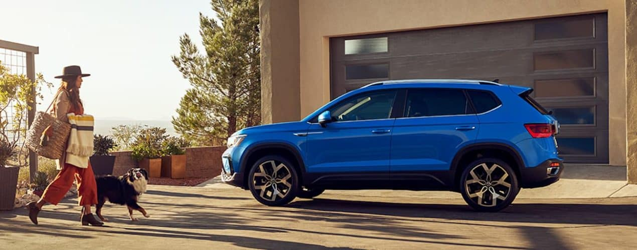 A woman and her dog are walking toward a blue 2022 Volkswagen Taos parked in front of a modern garage.