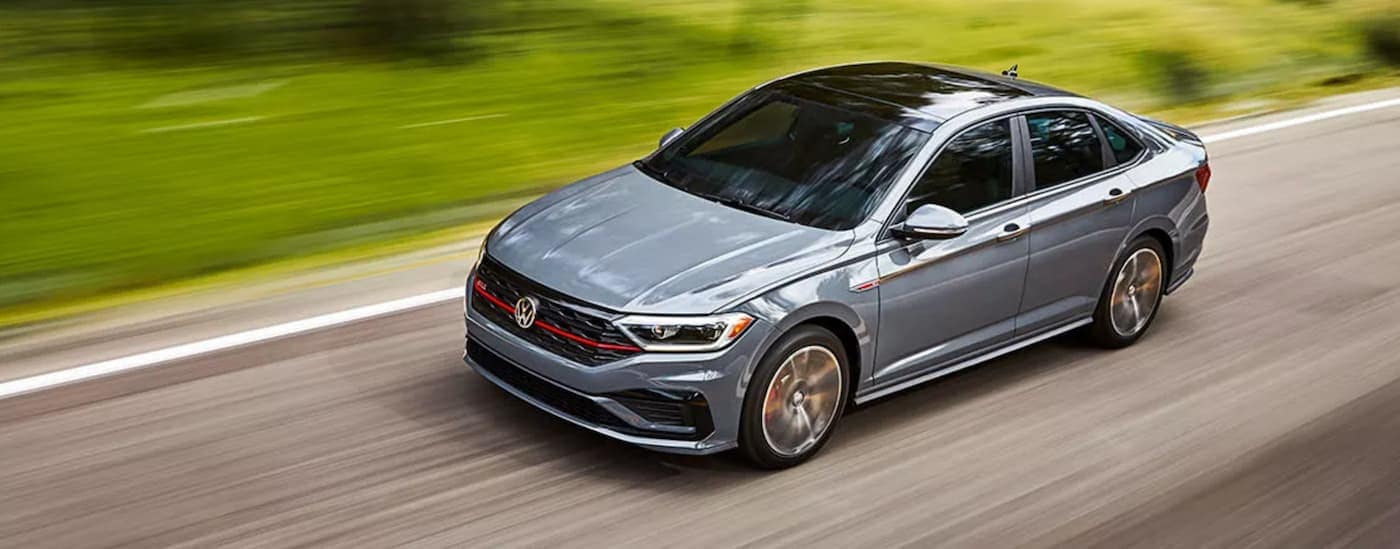 A grey 2021 Volkswagen Jetta GLI is driving past green grass after leaving a VW dealer.