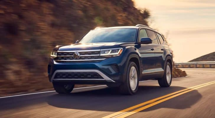 A blue 2021 Volkswagen Atlas is driving on a winding mountain road.