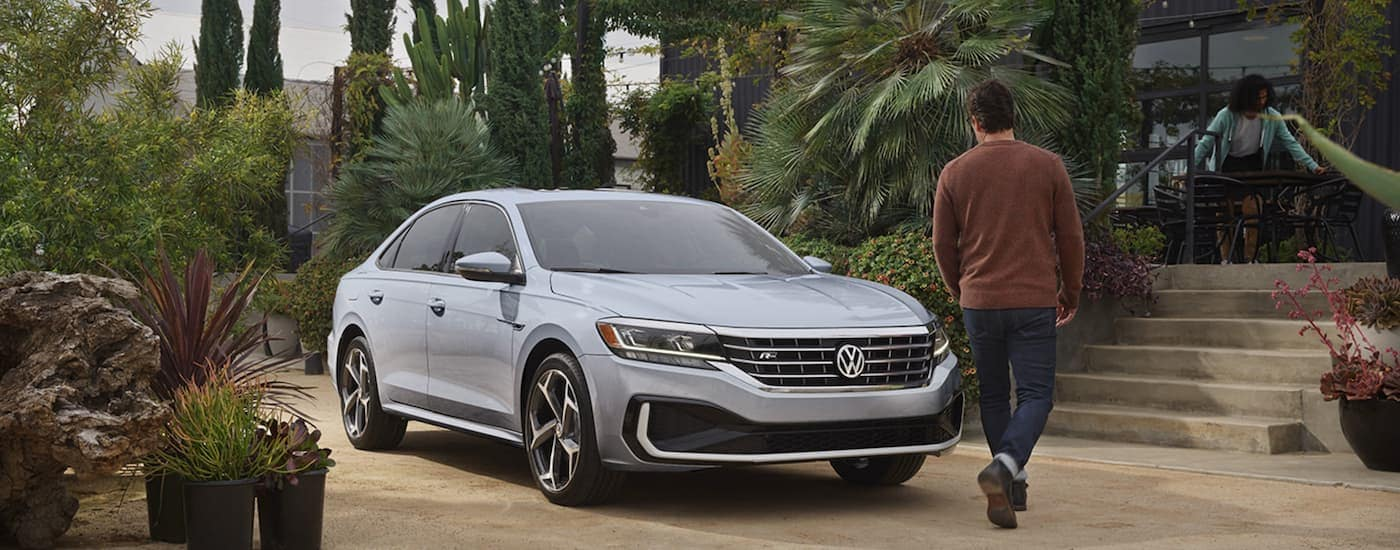 A man is walking toward a grey 2021 Volkswagen Passat parked in front of bushes after leaving a VW dealer near me.