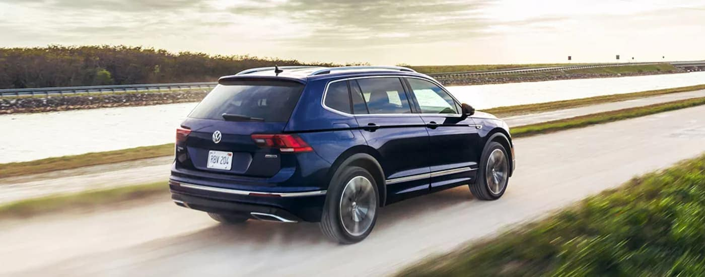 A blue 2021 Volkswagen Tiguan is driving on a dirt road along side a river.