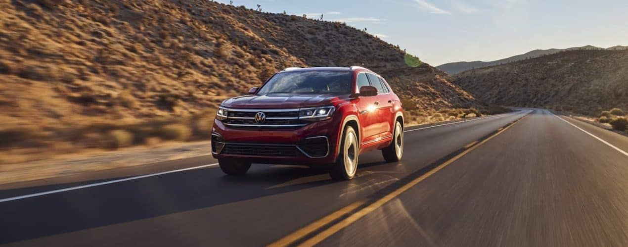 A red 2021 Volkswagen Atlas Cross Sport is driving on a road in front of hills.