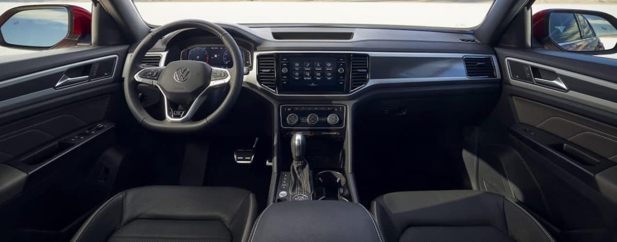 The black interior and dashboard of a 2021 Volkswagen Atlas Cross Sport are shown.
