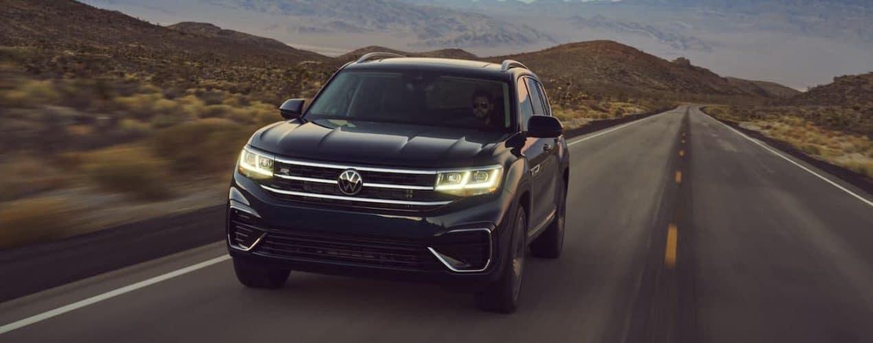 A black 2021 Volkswagen Atlas is driving in a desert in front of hills.