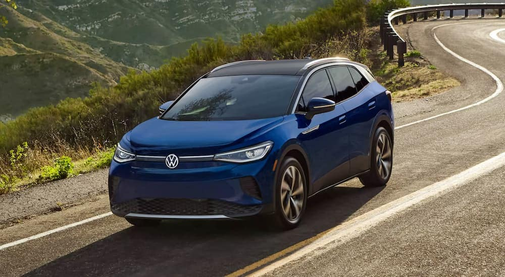 A blue 2021 Volkswagen ID.4 is on a test drive on a winding mountain road.