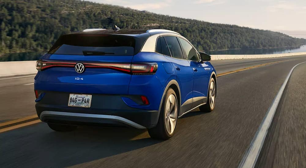 A blue Volkswagen ID.4 is shown from the rear driving toward a lake.