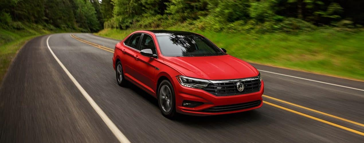 A red 2021 Volkswagen Jetta R-Line is driving down an empty tree lined road.
