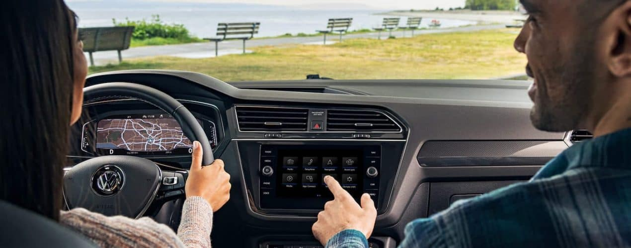 A close up shows passengers in a 2021 Volkswagen Tiguan using the infotainment systyem.