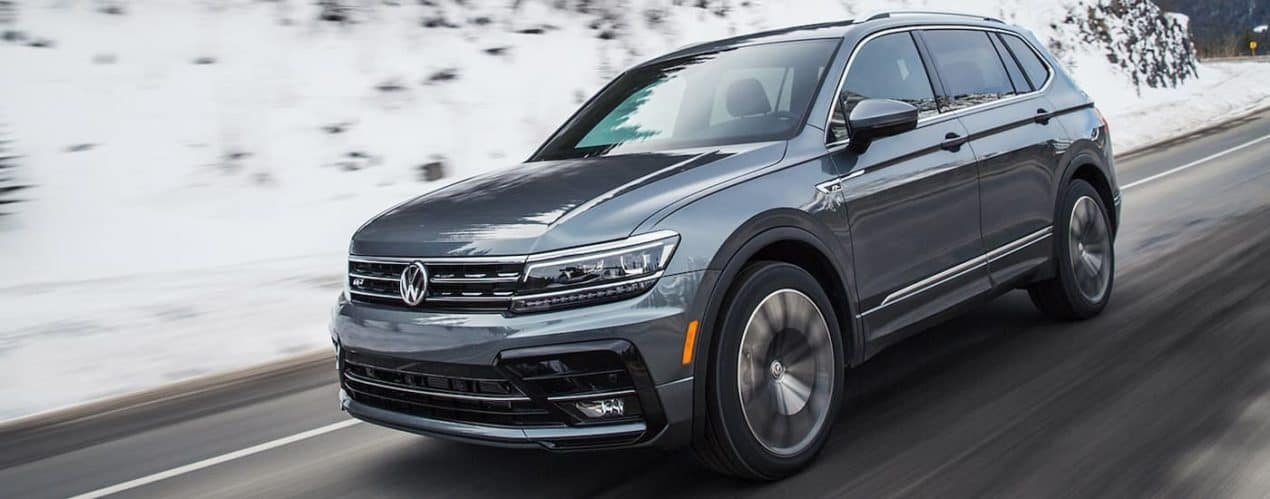 A gray 2021 Volkswagen Tiguan is shown from the side driving down a snowy road.