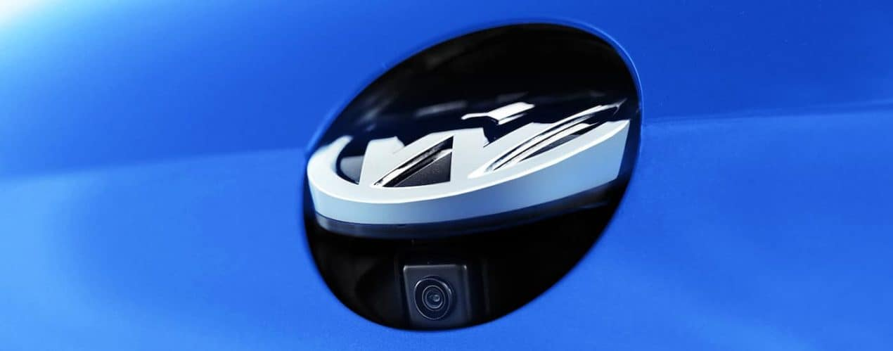 The badge and camera are shown on a blue 2021 Volkswagen Golf GTI.