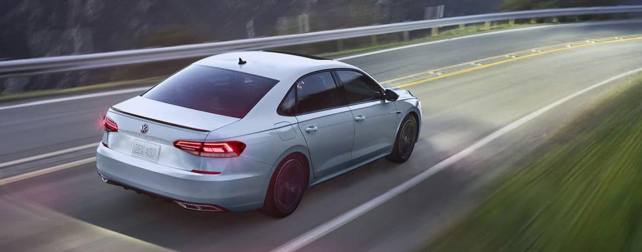 A silver 2021 Volkswagen Passat R-Line is shown from the rear driving down an empty road.