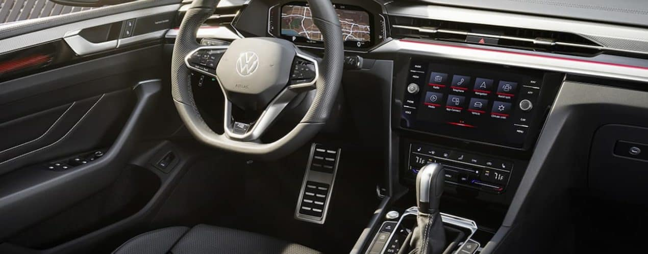 The black interior of a 2021 Volkswagen Arteon shows the steering wheel and infotainment screen.