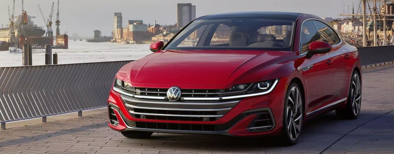 A red 2021 Volkswagen Arteon shown from the front is driving through a city.