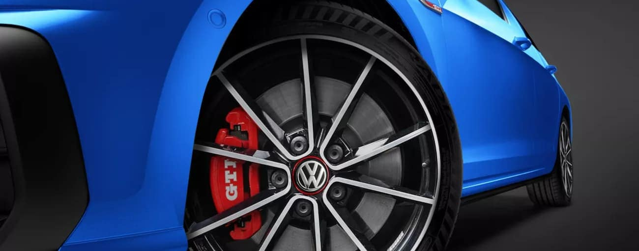 A blue 2021 Volkswagen Golf GTI shows the rear tire.
