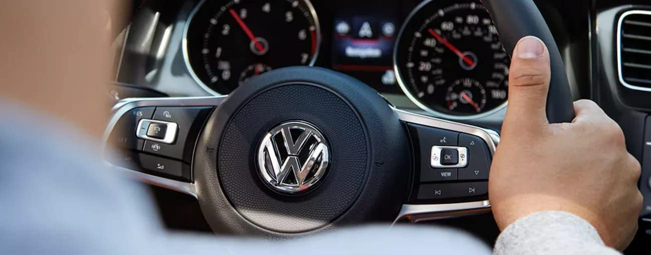 A close up shows a man driving a 2021 Volkswagen Golf GTI.