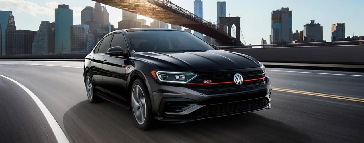 A dark grey 2021 Volkswagen Jetta GLI is shown driving under a bridge.