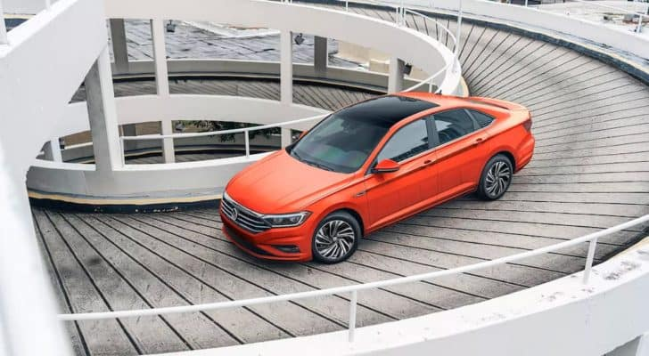 An orange 2021 Volkswagen Jetta is shown driving up a ramp after leaving a Seattle Volkswagen dealership.