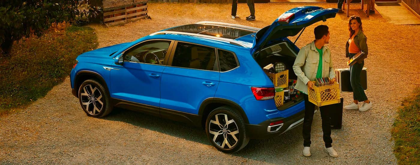A couple is shown removing boxes of records from the trunk of a blue 2021 Volkswagen Taos.