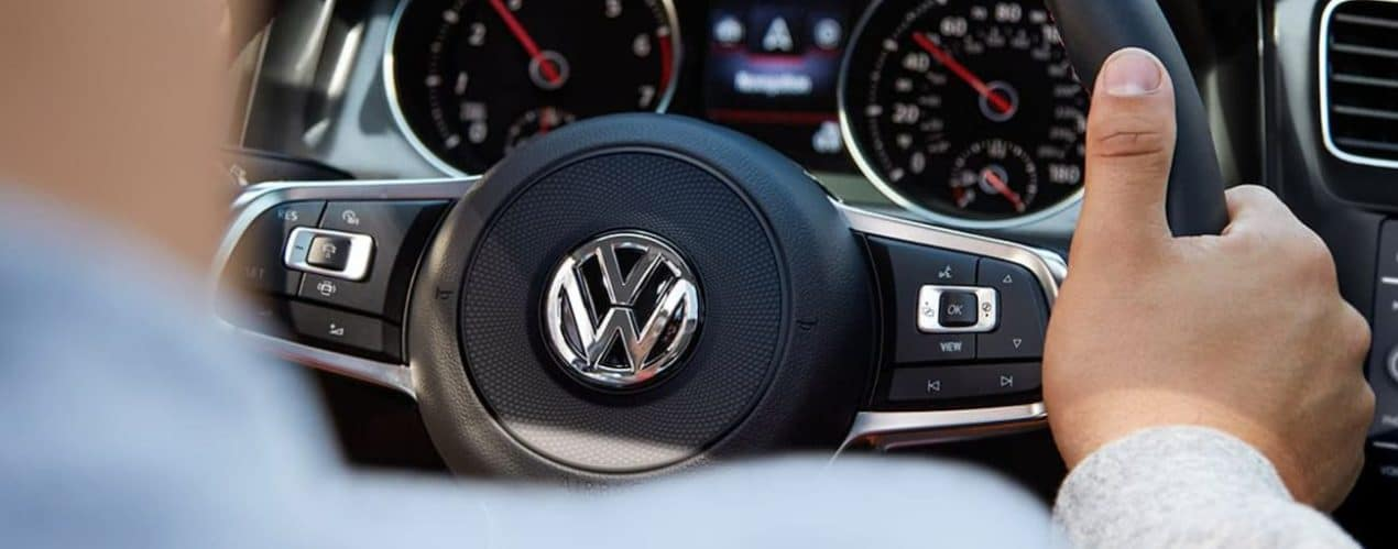 The interior of a 2022 Volkswagen Golf R shows the emblem on the steering wheel.