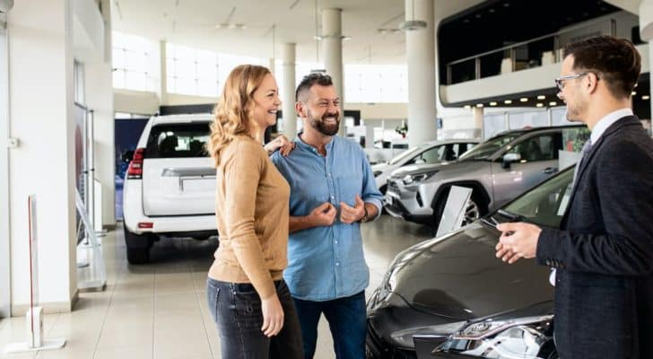 A couple is shown talking to a salesperson at a Washington Volkswagen dealer.