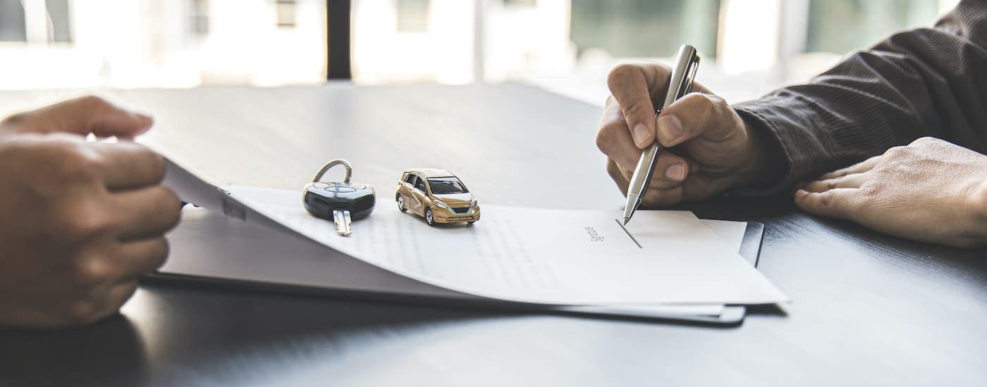 A close up shows paperwork , a toy car, and a car key.