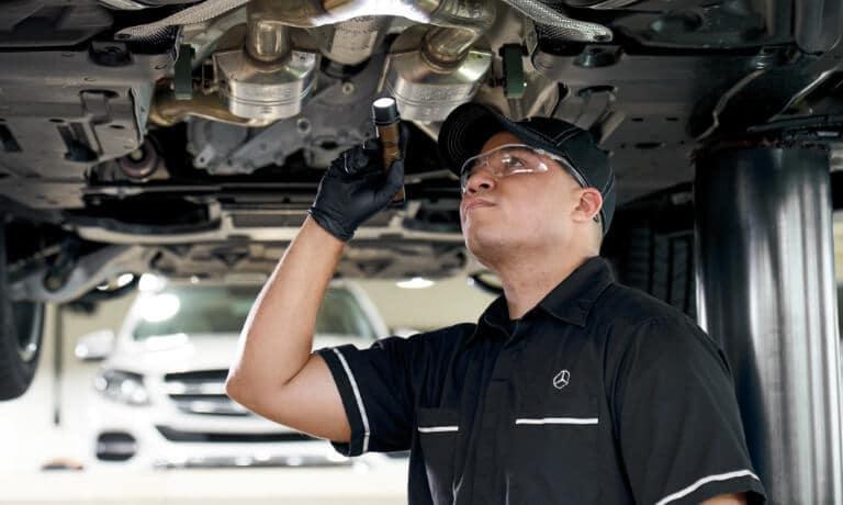 Mercedes-Benz Service Technician Inspecting Under Vehicle