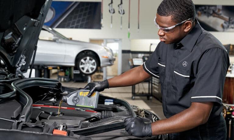 Mercedes-Benz Service Technician Under Hood Performing Oil Change