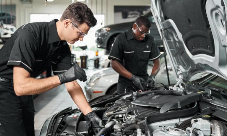 Mercedes-Benz Service Technicians Working Under Hood