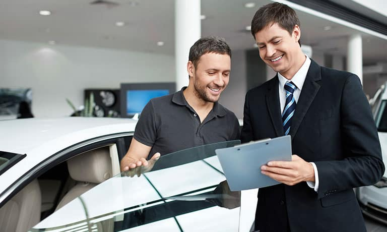 Salesperson and customer overlooking paperwork on clipboard