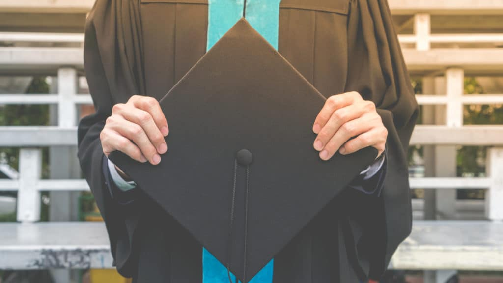 college graduate in black cap and gown with teal stole
