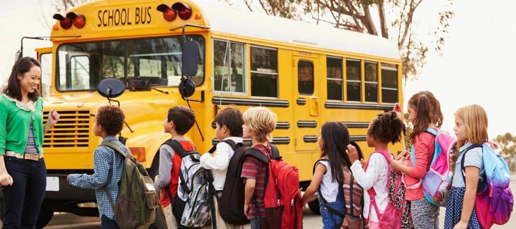 Children with Teacher by School Bus