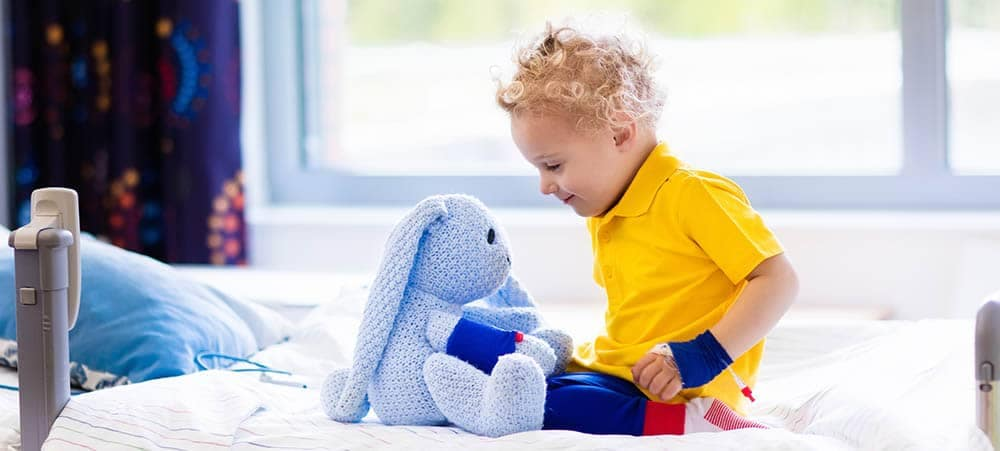 Little boy playing with a stuffed animal in a hospital room