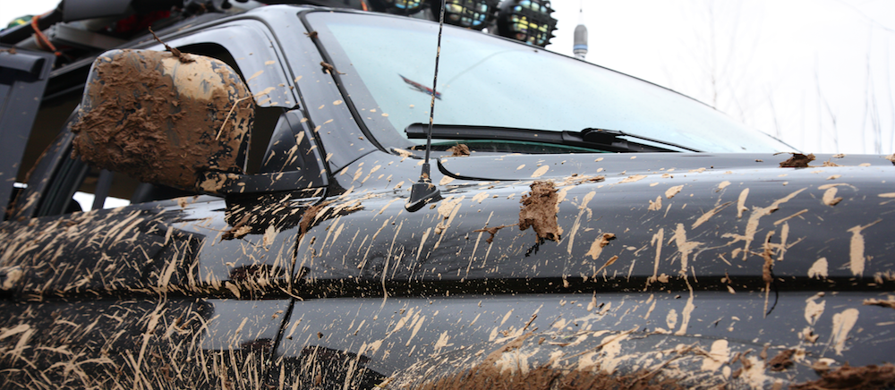 Black truck driving off road and covered in mud